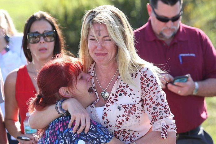 Parents wait for news after reports of a shooting at Marjory Stoneman Douglas High School in Parkland, Fla. (AP Photo/Joel Auerbach)