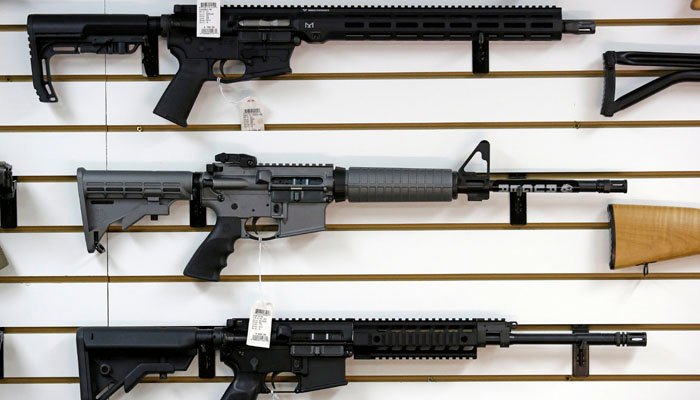 A Ruger AR-15 semi-automatic rifle, center, sits on display with other rifles on a wall in a gun shop Tuesday, Nov. 7, 2017, in Lynnwood, Wa