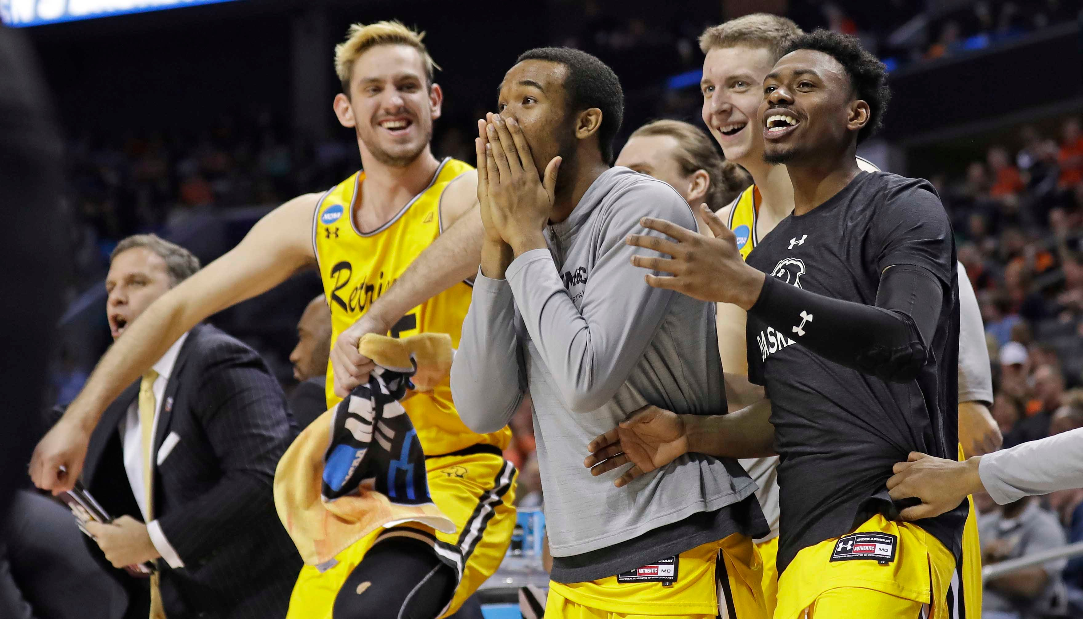 UMBC players celebrate a teammate's basket against Virginia during the second half of a first-round game in the NCAA men's college basketball tournament in Charlotte, N.C., Friday, March 16, 2018. (Source: AP Photo/Gerry Broome)