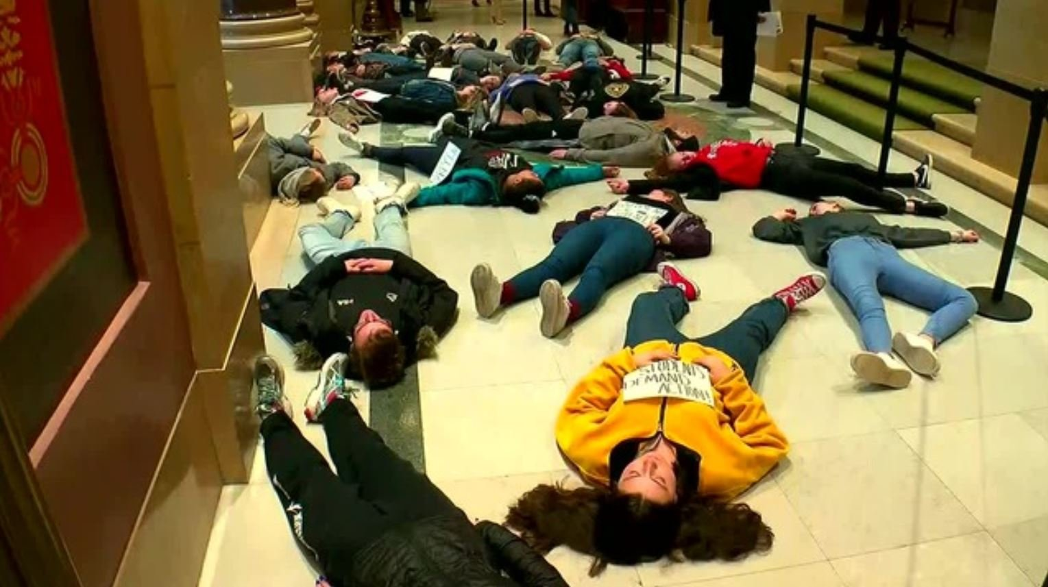 "Students staged a ""die-in"" protest of gun violence by lying motionless on the floor of Minnesota's capitol Thursday"