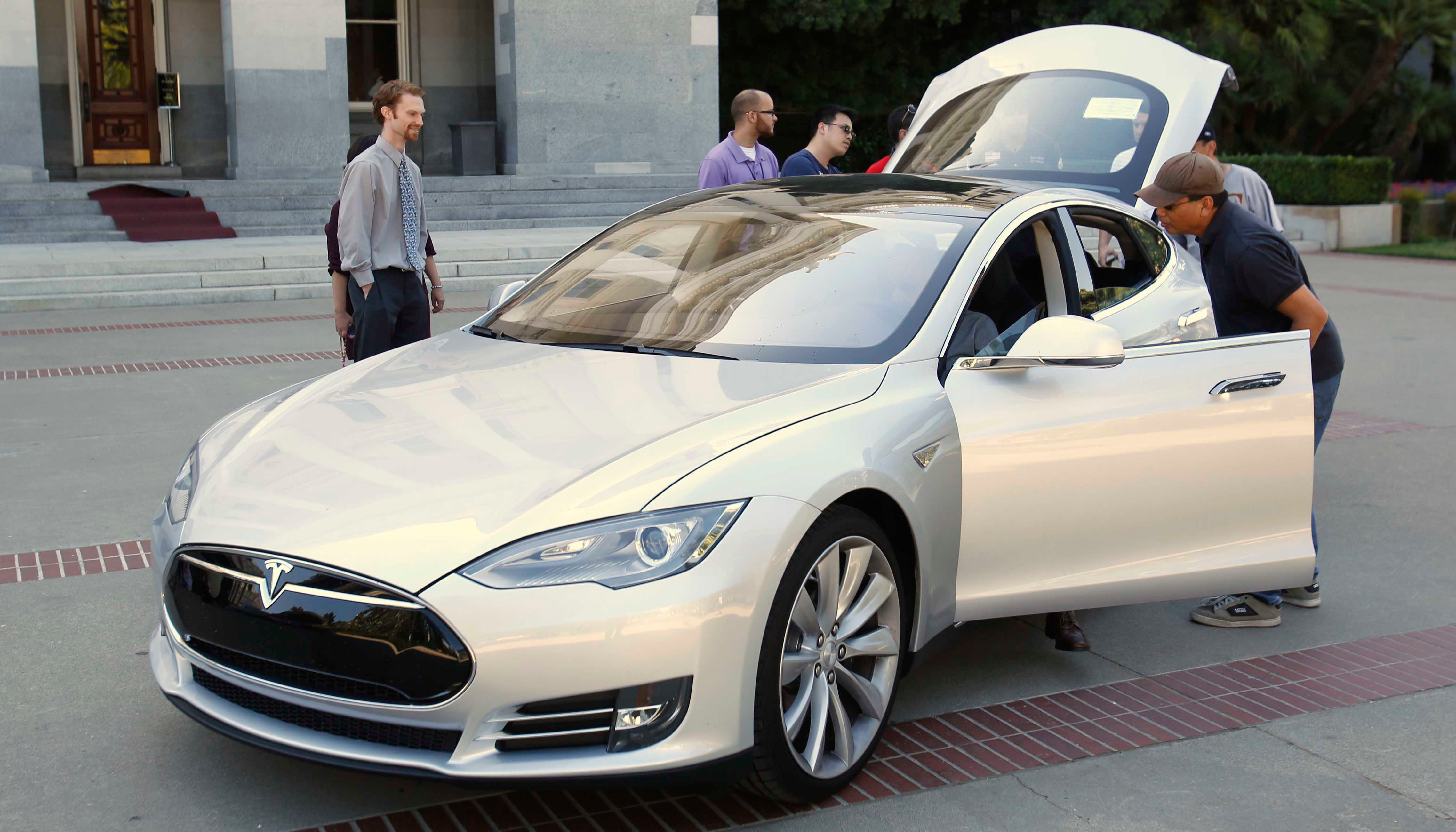 In this June 18, 2013 photo, visitors to Sacramento, CA, inspect the Tesla Motors Model S electric sedan. Tesla is recalling 123,000 Model S sedans built before April 2016 because of a power steering issue. (Source: AP Photo/Rich Pedroncelli, file)