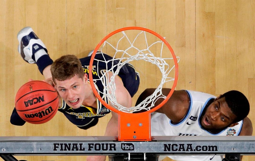 (AP Photo/David J. Phillip) Michigan forward Moritz Wagner, left, drives to the basket over Villanova forward Eric Paschall during the first half in the championship game of the Final Four NCAA college basketball tournament, Monday, April 2, 2018.