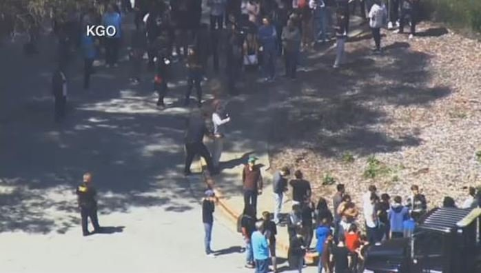 Police frisk YouTube employees as they are evacuated from their San Bruno campus after shots fired. (Source: KGO/CNN)