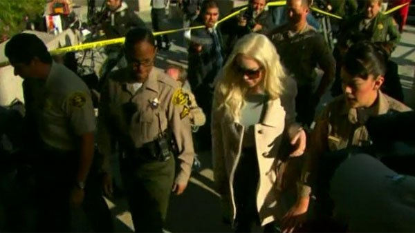 Lohan wore tortoiseshell glasses and a long coat over her blue sweater and black pants. (Source: CNN)