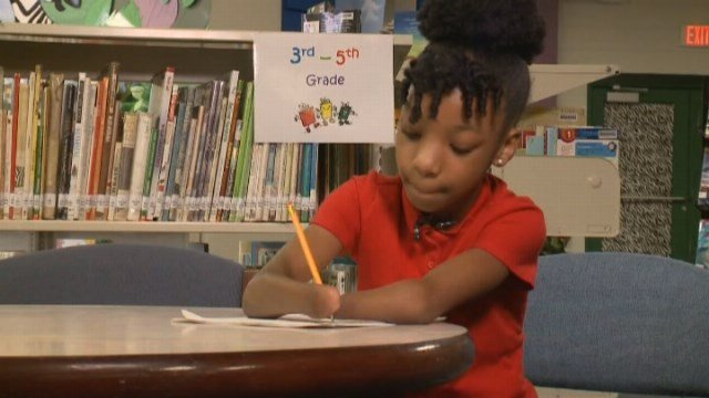 The third grader doesn't use prosthetics and has learned to hold a pencil between her two arms to write and draw. (Source: WTKR/CNN)