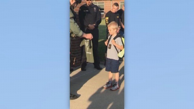 Five-year-old Dakota Pitts wore his father's badge and was presented a SWAT shirt on Monday. (Source: SAMANTHA PHEGLEY/SULLIVAN ELEMENTARY SCHOOL/CNN)