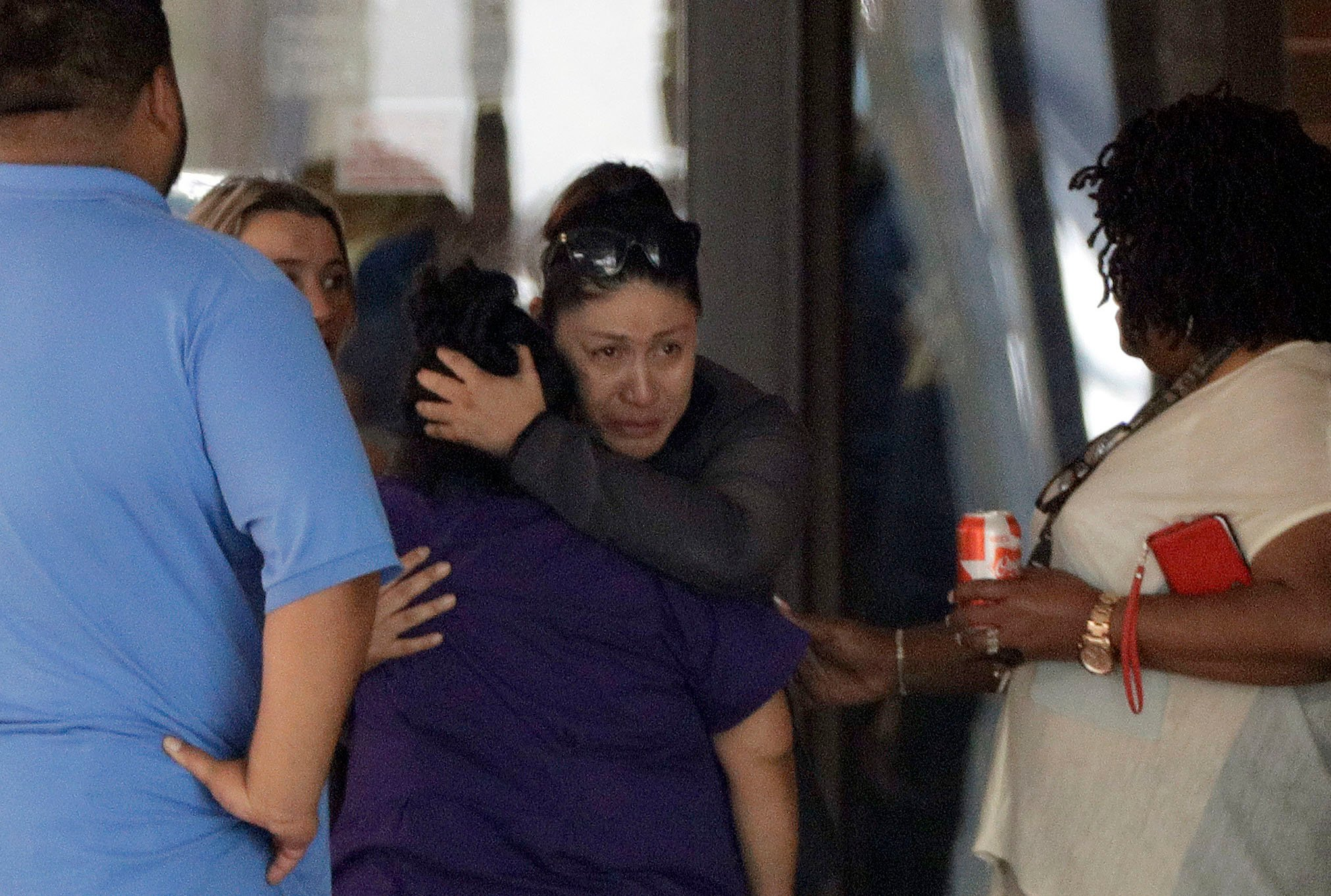 People react outside the unification center at the Alamo Gym, following a shooting at Santa Fe High School Friday, May 18, 2018, in Santa Fe, Texas. (AP Photo/David J. Phillip)