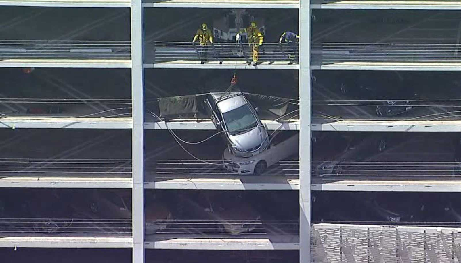 Crews removed a car dangling from the fourth floor of a California parking garage Monday. (Source: KABC/CNN)