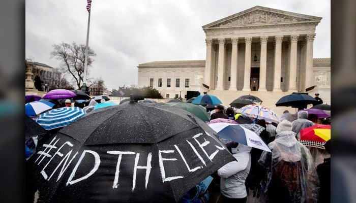 "A pro-abortion rights supporter holds an umbrella that reads ""#EndTheLies"" during a rally outside the Supreme Court in Washington March 20 as the Supreme Court hears arguments in a free speech fight. (AP Photo/Andrew Harnik)"