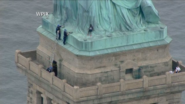 Liberty Island evacuated after statue base climber, banner