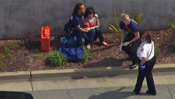 Police comfort woman after a gunman opened fire on the Oikos University campus Monday. (Source: KGO/CNN)