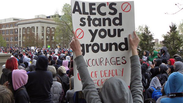 "At a rally for Trayvon Martin in Minneapolis on March 29, a protestor holds up a sign reading, ""ALEC's stand your ground encourages use of deadly force."" (Source: Fibonacci Blue/Flickr)"