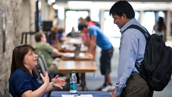 A student at the University of Illinois at Springfield speaks to a recruiter at a campus job fair. (Source: Jeremy Wilburn/Flickr)