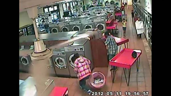 Parents and a Laundromat attendant work to free a baby from a washing to machine. (Source: YouTube)