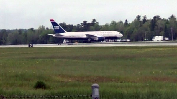 A U.S. Airways plane sits on a runway at Bangor International Airport in Bangor, ME. The plane was flying from Paris to Charlotte, NC, and was diverted because of a security threat. (Source: WLBZ/CNN)