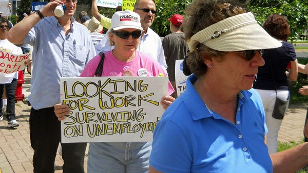 "A woman holds up a sign that says ""Looking for work surviving on unemployment,"" at a rally for unemployment insurance in Wisconsin in 2010. (Source: wisaflcio/Flickr)"