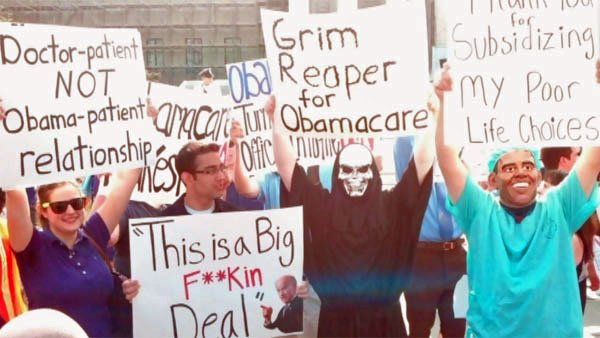 Protesters hold signs in protest outside the Supreme Court on June 28. (Source: CNN)