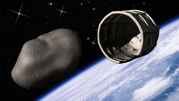 A mock-up of an asteroid and a concept asteroid harvester hovering over Earth.
