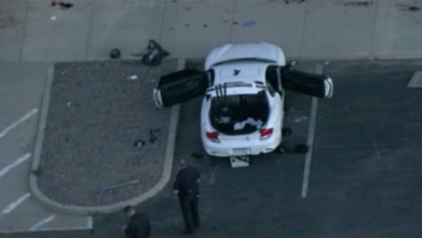 Police search a car associated with the alleged gunman behind the movie theater where 10 people were killed. (Source: CNN)