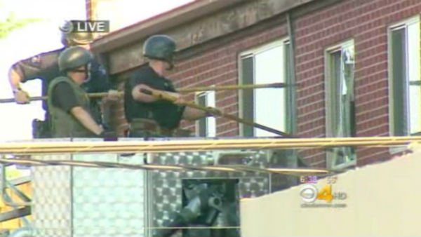 FBI enters the apartment of James Holmes who is suspected of opening fire in a movie theater in Aurora, CO. (Source: KCNC/CNN)