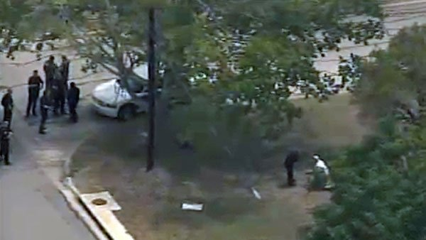 Aerials show police clustered on a street corner while a man appears to be examining a gun with a police officer on the right hand side of the image after a gunman opened fire near Texas A&M University. (Source: KLTV)