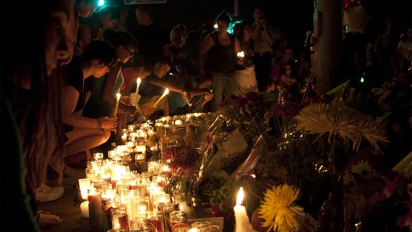 After a vigil at the Aurora Municipal Center, gatherers keep candles lit at the memorial for the victims of the 'Dark Knight Rises' shooting in Aurora, CO. (Source: Brian T. McGinn)