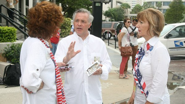 Scott Moore passes out fliers and cards advertising his new business to passersby outside the Republican National Convention. (Source: Jennifer Bowen/RNN)