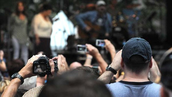 Armed with cameras, concert goers strain for the perfect shot of James Taylor at CarolinaFest2012. Unfortunately, Taylor was only able to play for 30 minutes before the rains came. (Source: Cecelia Hanley/RNN)