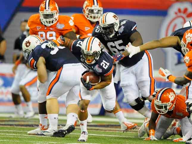 Tre Mason (21) runs through the line in the first half for Auburn against Clemson on Sept. 1 in Atlanta. (Source: Todd Van Emst/Auburn University)
