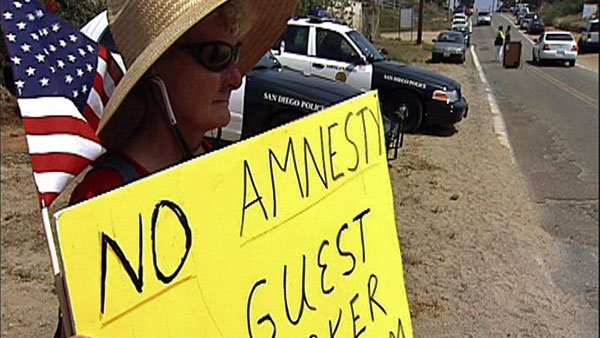 A woman holds a sign protesting against illegal immigration. (Source: KPBS-TV)