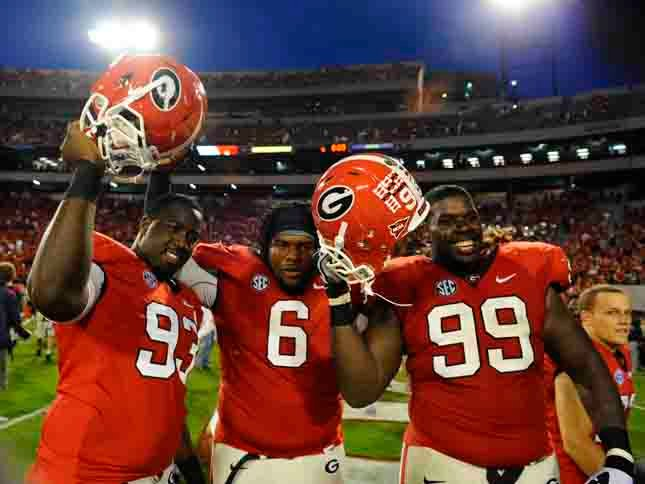 Georgia's Abry Jones (93), John Jenkins (6) and Kwame Geathers (99) celebrate a win over Tennessee. (Source: Georgia Athletics)