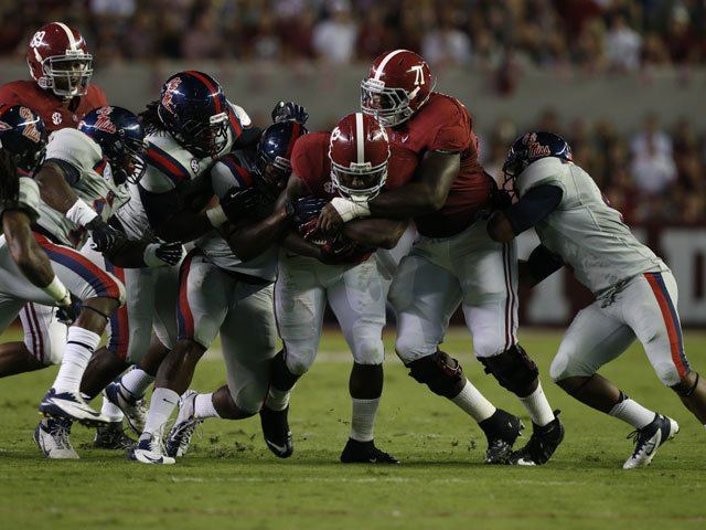 Alabama's Eddie Lacy (42) gets some help covering up the ball as Ole Miss defenders move to tackle him. (Source: Alabama Athletics Communications)