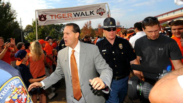 Gene Chizik walks through an isolated faction of Auburn fans who still tolerate his existence prior to the Tigers' loss to Ole Miss. (Source: Todd Van Emst/Auburn University)