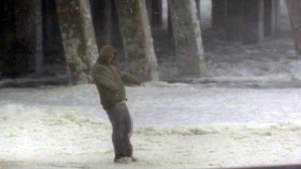 A person in Kill Devil, NC is hit with high winds from Hurricane Sandy. The storm is expected to make landfall late Monday. (Source: WSOC/CNN)