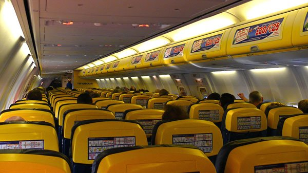 The cabins of Ryanair's planes are distinct, covering the overhead bins in ads and posting safety instructions in the backs of headrests. (Source: Ruthann/Wikimedia)