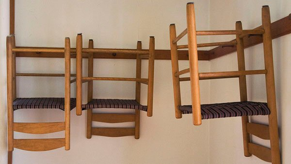 These are Shaker chairs hanging upside-down on a wall somewhere for some reason. The Shakers bounced back from failed apocalypse predictions to make top-notch furniture. (Source: Wikimedia Commons)