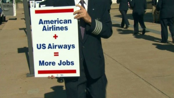 American Airlines pilots hold signs supporting a merger with US Airways outside of Ronald Reagan Washington National Airport. (Source: CNN)