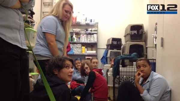 A group huddles in the back room of a pet store at the Clackamas, OR, Town Center after a gunman opened fire. (Source: KPTV)