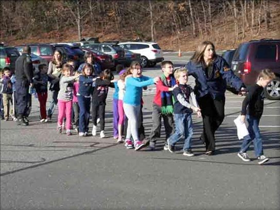 Children at Sandy Hook Elementary School are evacuated by law enforcement officials in Newtown, CT, on Dec. 14, 2012. (Source: The Newtown Bee)