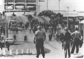 "Civil Rights marchers were met at the base of the Edmund Pettus Bridge on ""Bloody Sunday"" March 7, 1965. (Source"" Department of Justice/Wikipedia)"