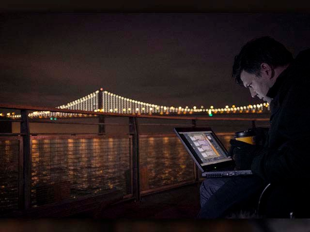 Artist Leo Villareal works on his computer with the Bay Bridge lit up in the background. (Source:  Lucas Saugen)