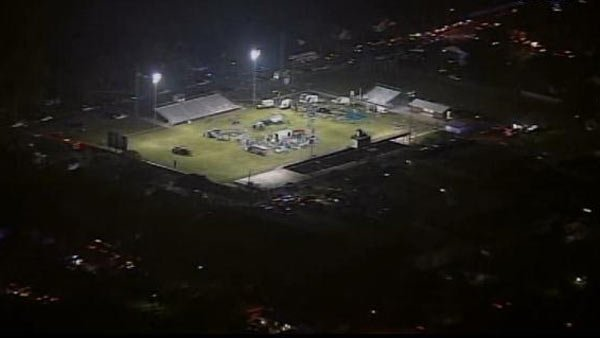 An aerial view of a football field where ambulances set-up emergency care units. The football field was eventually evacuated and the triage relocated. (Source: KTVT/CNN)
