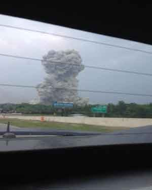 A cloud of smoke rises over a fertilizer plant that exploded in West, TX. (Source: DFW Scanner)