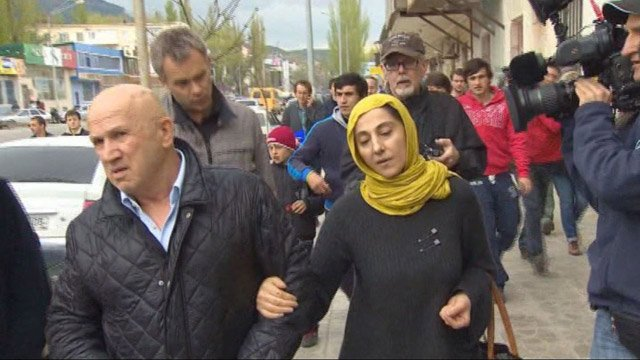 Zubeidat Tsarnaeva, the mother of the Boston Marathon bombing suspects, is followed by reporters Tuesday. (Source: CNN)