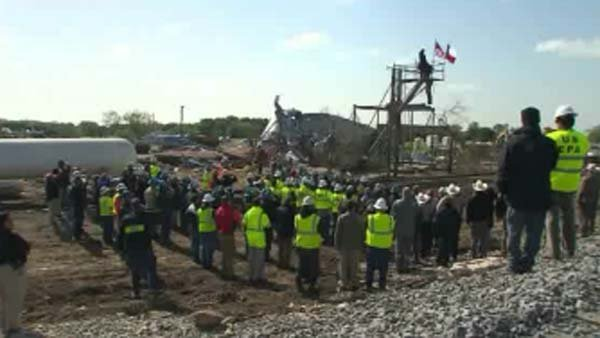Workers and investigators take a moment of silence for the lives lost after the plant explosion. (Source: CNN)