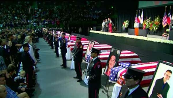 A row of 12 coffins, each draped with a flag honoring the lives lost during the West, TX plant explosion. (Source: CNN)
