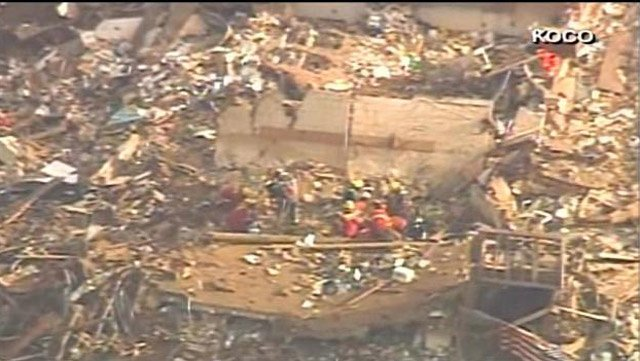 Emergency staff searches through rubble after a massive tornado struck the Oklahoma City metropolitan area Monday. (Source: KOCO/CNN)
