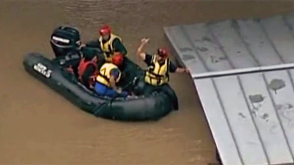 A rescue worker gives the thumbs up after pulling someone stuck on top of a roof into their boat. (Source: KENS/CNN)