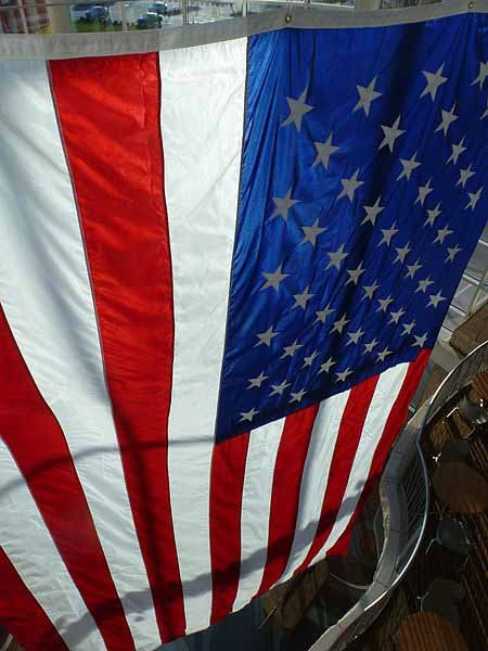 An American flag hangs over the Flint Hills Discovery Center in Manhattan, KS. (Source: Wikimedia Commons)