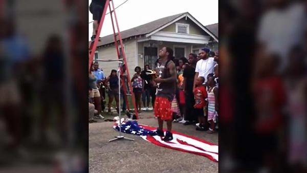 Lil' Wayne standing on the American flag during a scene in his music video. (Source: YouTube)